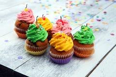 Bigné saporiti su fondo di legno Bigné di compleanno in arcobaleno Fotografia Stock Libera da Diritti