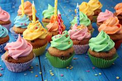 Bigné saporiti su fondo di legno Bigné di compleanno in arcobaleno Immagini Stock