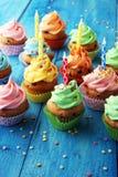 Bigné saporiti su fondo di legno Bigné di compleanno in arcobaleno Fotografie Stock