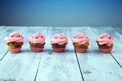 Bigné saporiti su fondo di legno Bigné di compleanno nel colore rosa Fotografia Stock Libera da Diritti