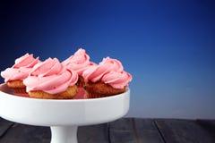 Bigné saporiti su fondo di legno Bigné di compleanno nel colore rosa Immagine Stock