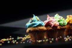 Bigné saporiti su fondo scuro Bigné di compleanno in arcobaleno c Immagini Stock