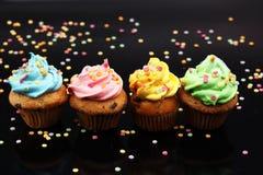 Bigné saporiti su fondo scuro Bigné di compleanno in arcobaleno c Fotografia Stock