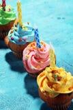 Bigné saporiti sulla tavola Bigné di compleanno nei colori dell'arcobaleno Fotografie Stock Libere da Diritti