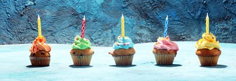 Bigné saporiti sulla tavola Bigné di compleanno nei colori dell'arcobaleno Immagini Stock