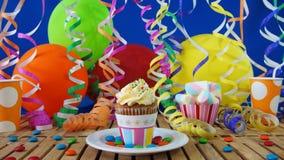 Bigné sulla tavola di legno rustica con fondo dei palloni variopinti, delle tazze di plastica e delle caramelle Fotografia Stock Libera da Diritti
