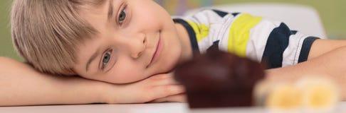Bigné sveglio del cioccolato e del ragazzo Fotografie Stock