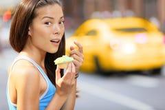 Bigné - donna presa mangiando lo spuntino del bigné Fotografia Stock