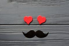 Bigode de papel e corações vermelhos no fundo de madeira cinzento Fotos de Stock Royalty Free