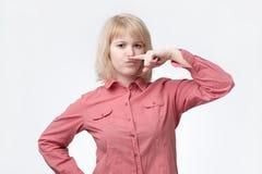 Bigote rubio de la demostración de la mujer con el finger Ella se está sintiendo mal el olor foto de archivo
