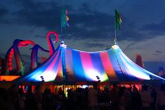 Bigtop festival tent twilight sky. A large colorful tent topped by two flags is silhouetted by a dramatic twilight sky at a summer music festival in the UK Stock Image