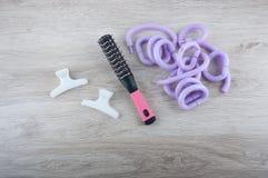 Bigudíes, cepillo y vueltas de la peluquería del salón en la tabla Fotos de archivo