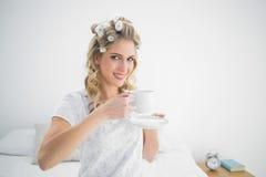 Bigudíes de pelo que llevan bastante rubios relajados que sostienen el café Foto de archivo libre de regalías