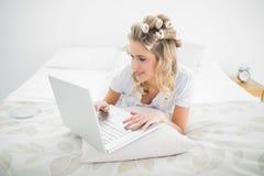 Bigudíes de pelo que llevan bastante rubios relajados usando el ordenador portátil Imagen de archivo libre de regalías
