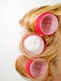 Bigudíes rojos en pelo rubio Imagenes de archivo