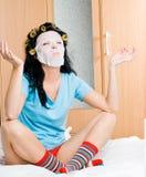 Bigudíes de pelo de la mujer que desgastan joven y una máscara Imagenes de archivo