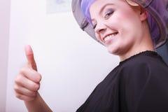 Bigudíes sonrientes de los rodillos del pelo de la mujer que muestran el pulgar encima de un salón de belleza más seco Fotos de archivo libres de regalías