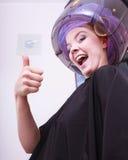 Bigudíes sonrientes de los rodillos del pelo de la mujer que muestran el pulgar encima de un salón de belleza más seco Foto de archivo libre de regalías