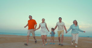 Bih happy family running on the beach. Steadicam shot of a big family of parents, son and grandparents holding hands and running on the beach. Happy vacation stock video footage