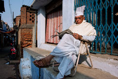 BIHAR, INDIA: Elderly asian man reads a newspaper outdoor at the evening Stock Photo