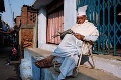 BIHAR INDIEN: Den äldre asiatiska mannen läser en tidning som är utomhus- på aftonen Arkivfoto
