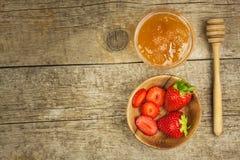 Bihonung och nya jordgubbar Söt mat Försäljningar av honung Arkivbild