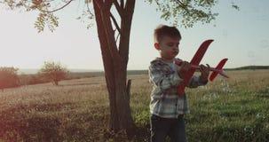 Bij aard op zonnige dag het charismatische jongen spelen grappig met een vliegtuig, bellen die overal vliegen stock footage