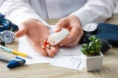 Bij artsen toont de benoemingsarts geduldige capsules, die in hand van container met nadruk op hand met drugs leegmaakten Sce royalty-vrije stock fotografie