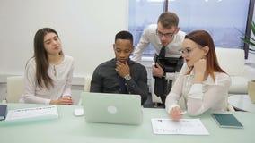 Bij bureau in bureau bekijkt het multi-etnische team met een leider laptop stock footage