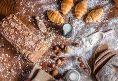 Bij de bakkerij, stilleven met minicroissants, brood, melk, noten en bloem Stock Foto