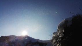 Bij de bodem van een donkere klip zoeken wij een manier aan de zon De stralen van de zon maken hun manier door de blizzard Royalty-vrije Stock Foto