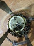 Bij de bodem van het glas het Frans is de pers een stuk van citroen en de theebladen worden gegoten stock afbeeldingen