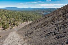 Bij de bovenkant van Cinder Cone, het Nationale Park dat van Lassen terug onderaan de proef en over het bos kijkt stock foto