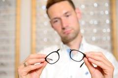 Bij de jonge mens van de opticienwinkel met gebroken glazen Royalty-vrije Stock Fotografie
