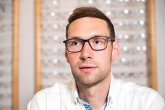Bij de jonge mens van de opticienwinkel met nieuwe glazen Stock Foto's