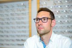 Bij de jonge mens van de opticienwinkel met nieuwe glazen Stock Fotografie