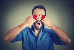 Bij de liefdemens die zijn ogen behandelen met handen stock foto