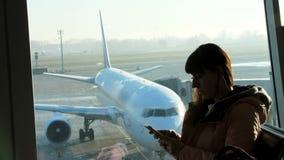 Bij de luchthaven, in de wachtkamer, tegen de achtergrond van een venster die de vliegtuigen en de baan, tribunes overzien stock footage