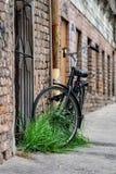Bij de oude baksteen bouw sloten de goten met een slot de zwarte fiets aan royalty-vrije stock afbeeldingen