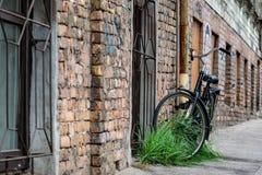 Bij de oude baksteen bouw sloten de goten met een slot de zwarte fiets aan stock fotografie
