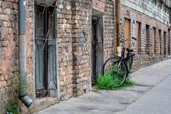 Bij de oude baksteen bouw sloten de goten met een slot de zwarte fiets aan stock foto's