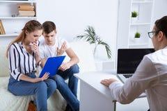 Bij de psycholoog Beautiful zit het jonge paar op laag en koestert terwijl de arts maakt royalty-vrije stock afbeelding