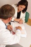 Bij de spreekkamer - Arts en patiënt Stock Afbeelding