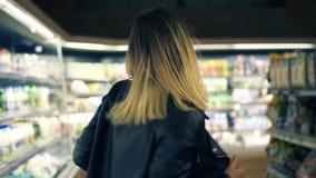 Bij de supermarkt: gelukkige jonge vrouw in zwarte jasjedansen door goederen en zuivelproducten op de planken whirling stock footage