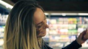 Bij de supermarkt: het gelukkige jonge meisje grappige dansen tussen planken in supermarkt Blondemeisje jeans dragen en zwarte di stock video
