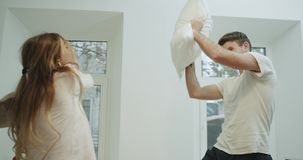 Bij het comfortabele charismatische het paar van de slaapkamerclose-up spelen grappig met twee kussens stock video