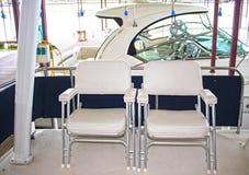 Bij het Partijdok - Mening van twee bootstoelen op achterdiedek van kruiser in jachthaven met een andere boot in vage box volgend Royalty-vrije Stock Foto