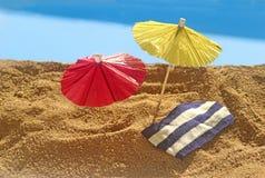 Bij het strand, met document parasols en blauw water Stock Foto