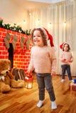 Bij Kerstmis de kinderen in kappen van Santa Claus door fireplac Stock Afbeelding