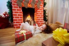 Bij Kerstmis het krullende meisje liggen dichtbij de open haard met GIF Stock Foto